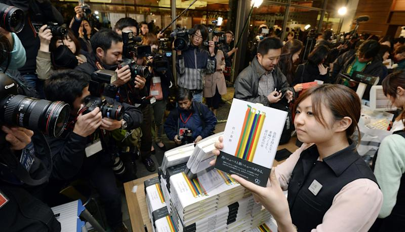 """A shop clerk poses with a copy of the book """" Colorless Tsukuru Tazaki and his years of pilgrimage, """" the latest novel by Japanese author Haruki Murakami for media at a book store in Tokyo Friday, April 12, 2013. Murakami's new novel, first in three years, went on sale on Friday. (AP Photo/Kyodo News)"""