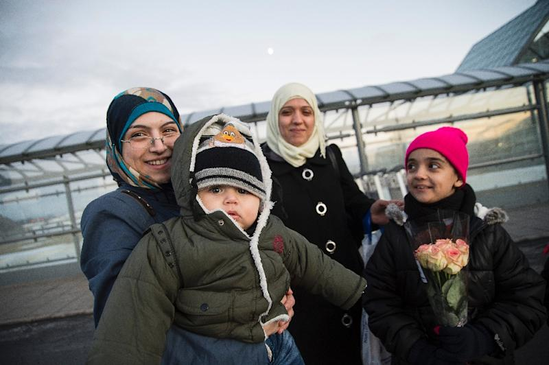 A woman with a child, part of a group of Syrian refugees, arrives in Iceland on January 19, 2016 at Keflavik airport (AFP Photo/Haraldur Guðjónsson)