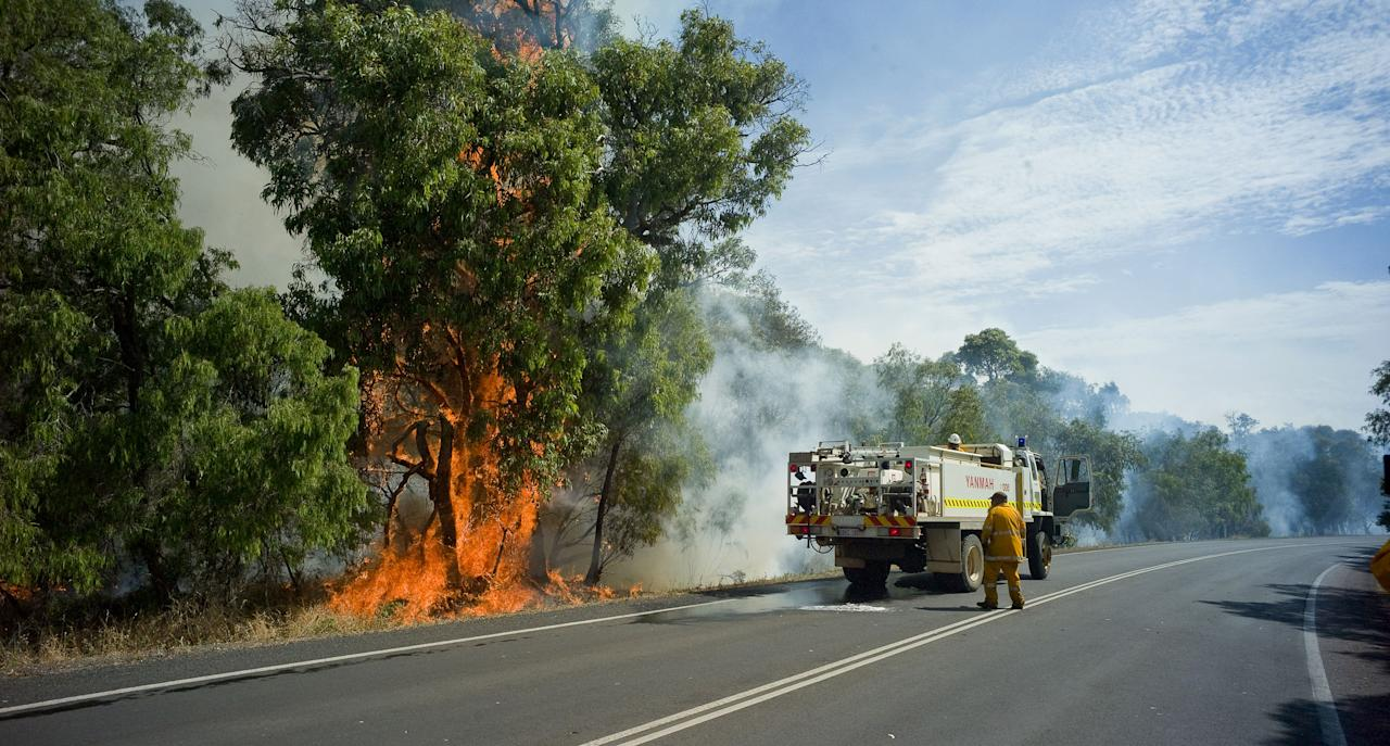 MARGARET RIVER, AUSTRALIA - NOVEMBER 24:  Fire fighters battle a breakout after a bush fire swept through the area on November 24, 2011 in Margaret River, Australia. Over 200 residents from Prevelly have gathered on a beach near to Margaret River's mouth as the blaze forced them from their houses. The bushfire has already destroyed over 1000 hectares north of Margaret River. According to WA's Department of Conservation (DEC) several homes have been destroyed so far. (Photo by Tony McDonough-Pool/Getty Images)