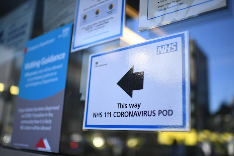 A sign points the way to a NHS 111 Coronavirus Pod at The Royal London Hospital in London on March 23, 2020. - Prime Minister Boris Johnson warned on Sunday he may impose tougher controls on the British public as packed parks, markets and cafes at the weekend showed thousands of people defying government warnings about social distancing. The PM gave notice of potential tougher action as the latest health department figures revealed that 281 people had now died from COVID-19 in the UK, an increase of almost 50 fatalities in the past 24 hours, and there are 5,683 confirmed cases. (Photo by DANIEL LEAL-OLIVAS / AFP) (Photo by DANIEL LEAL-OLIVAS/AFP via Getty Images)