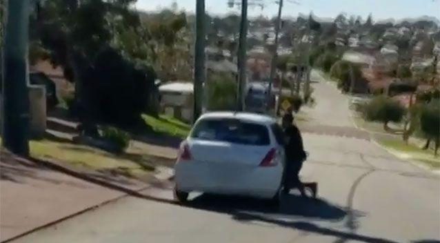 Suddenly the car takes off and the man is dragged along the road. Source: 7 News
