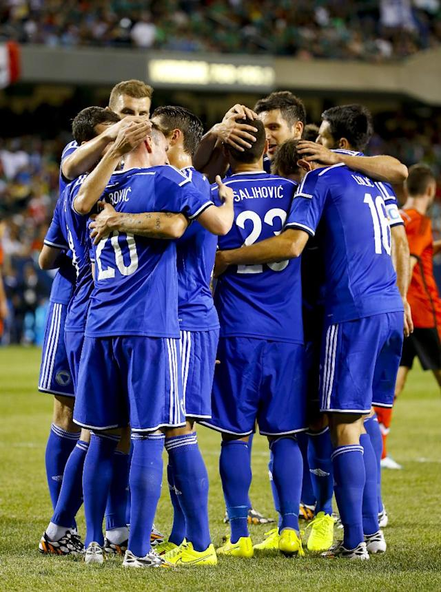 Bosnia-Herzegovina forward Izet Hajrovic (20) is congratulated by teammates after scoring against Mexico during the first half of an international friendly soccer match at Soldier Field in Chicago, Tuesday, June 3, 2014