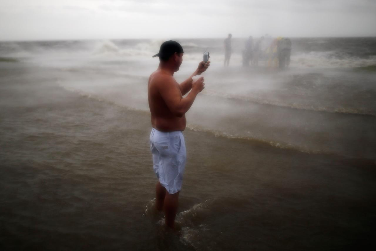 NEW ORLEANS, LA - AUGUST 28:  A man takes a photograph of flood waters near Lake Pontchatrain as Hurricane Isaac approaches on August 28, 2012 in New Orleans, Louisiana.  Hurricane Isaac is expected to make landfall later today along the Lousiana coast.  (Photo by Chris Graythen/Getty Images)