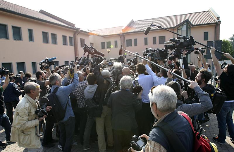 "Reporters gather outside the ""Sacra Famiglia"" foundation in Cesano Boscone, near Milan, Italy, where Silvio Berlusconi arrived to carry out a court order to help the elderly, Friday, May 9, 2014. Former Premier Berlusconi has arrived at a facility for Alzheimer's patients to begin his first four-hour community service stint as part of a tax fraud sentence. Berlusconi entered the Sacra Famiglia center at the appointed hour Friday without comment to the dozens of journalist outside, and was escorted inside by an administrator.The three-time former premier was ordered to perform four hours of community service a week for a year, after his four-year sentence was reduced to one by a general amnesty. (AP Photo/Antonio Calanni)"