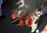 Supporters of the religious student group, Islami Jamiat Tulba, burn a representation of the French flag with an image of French President Emmanuel Macron during a protest against the publishing of caricatures of the Prophet Muhammad they deem blasphemous, in Peshawar, Pakistan, Tuesday, Oct. 27, 2020. (AP Photo/Muhammad Sajjad)