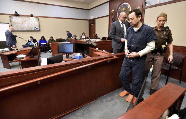 "Larry Nassar is removed from the witness stand after he listened to some of his victims make ""impact statements"" during a sentencing hearing in front of Judge Rosemarie Aquilina in district court. (AP)"