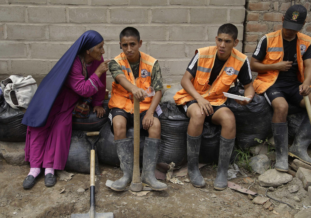 <p>A woman from a religious sect, who lost her home to flooding, gives a religious lecture to soldiers taking a rest from cleaning a clogged river in the Chosica district of Lima, Peru, Sunday, March 19, 2017. Intense rains and mudslides over the past three days have wrought havoc around the Andean nation and caught residents in Lima, a desert city of 10 million where it almost never rains, by surprise. (Martin Mejia/AP) </p>