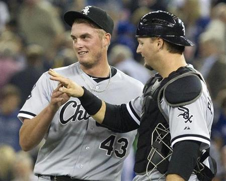 Chicago White Sox catcher A.J. Pierzynski (R) congratulates pitcher Addison Reed on the save after they beat the Toronto Blue Jays in their American League MLB baseball game in Toronto August 14, 2012. REUTERS/Fred Thornhill