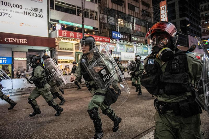 TOPSHOT - Riot police run towards protesters on Nathan road in Hong Kong on December 1, 2019. - Police fired tear gas and pepper spray in Hong Kong on December 1 as tens of thousands of black-clad protesters flooded into the streets, a week after pro-democracy candidates scored a landslide local election victory. (Photo by NICOLAS ASFOURI / AFP) (Photo by NICOLAS ASFOURI/AFP via Getty Images)