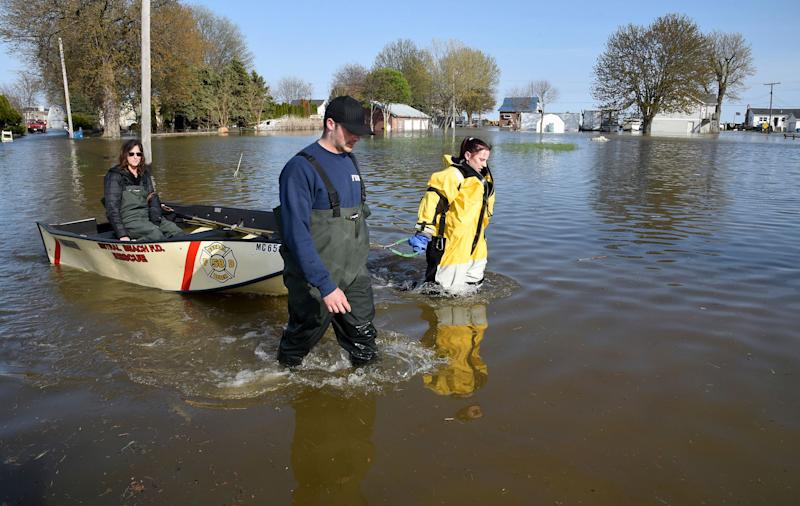 Estral Beach Firefighters Eric Bruley, left, and Courtney Millar wade through waters as they escort Bruley's mother Carla, home after work Wednesday, May 8, 2019 down Lakeshore Dr. in the south end of Estral Beach in Berlin Township, Michigan.
