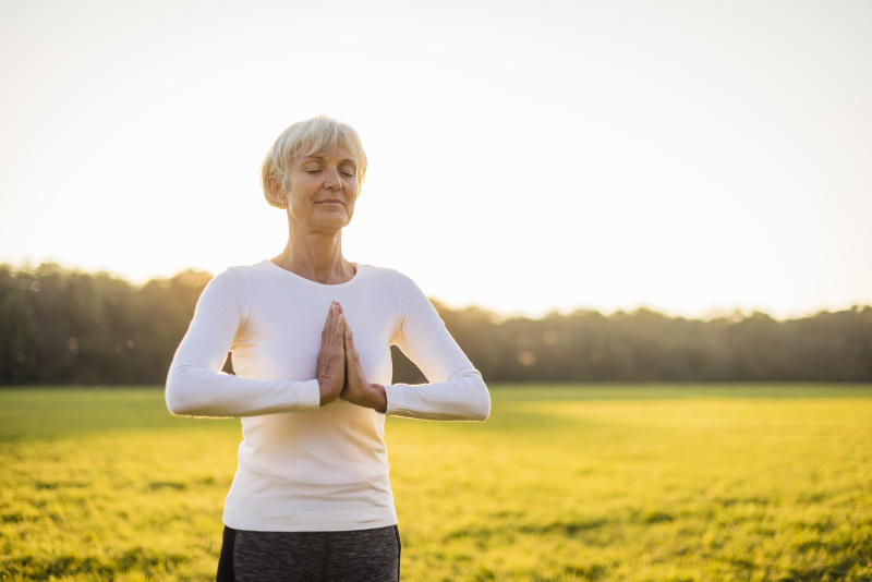 Senior woman doing yoga on rural meadow at sunset