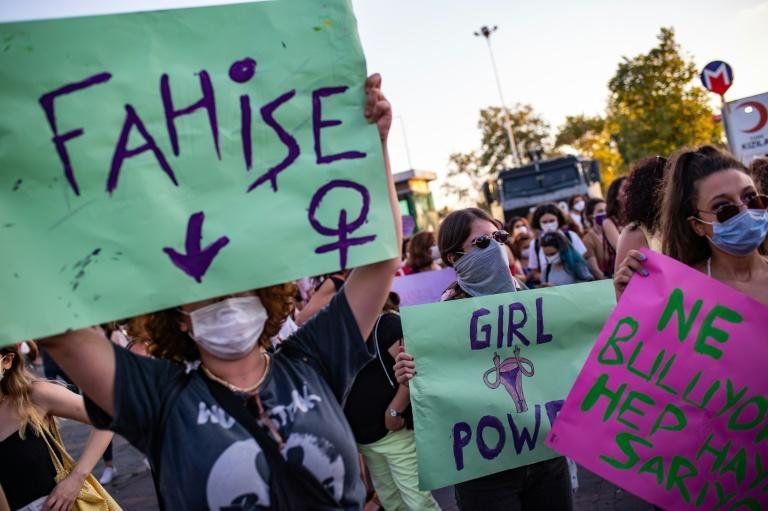 "Demonstrators wearing protective face masks hold up placards reading ""Whore"" (L) and ""Girl Power"" during a demonstration for a better prevention of violence against women, in Istanbul, Turkey"