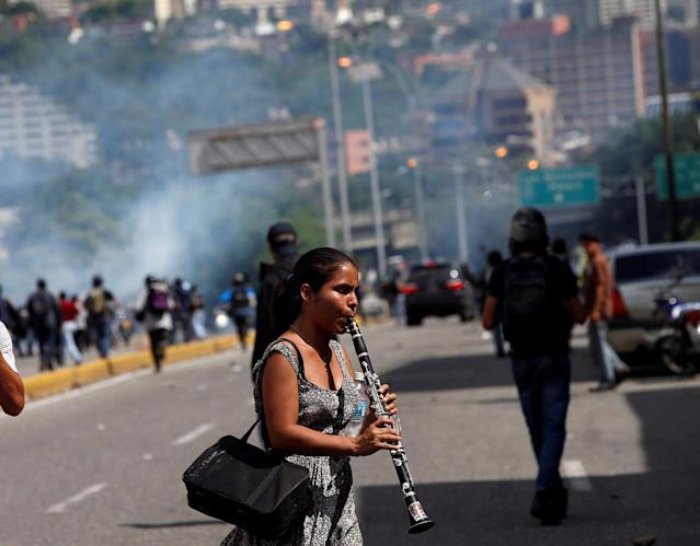 <p>A girl plays the instrument during clashes with security forces at a rally against Venezuelan President Nicolas Maduro's government in Caracas, Venezuela, July 6, 2017. (Photo: Andres Martinez Casares/Reuters) </p>