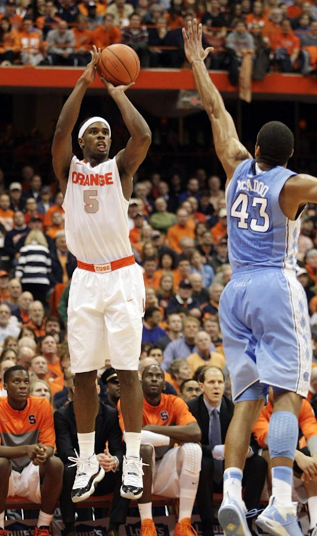 Syracuse's C.J. Fair, left, shoots for three against James Michael McAdoo, right, in the second half of an NCAA college basketball game in Syracuse, N.Y., Saturday, Jan. 11, 2014. Syracuse won 57-45. (AP Photo/Nick Lisi)