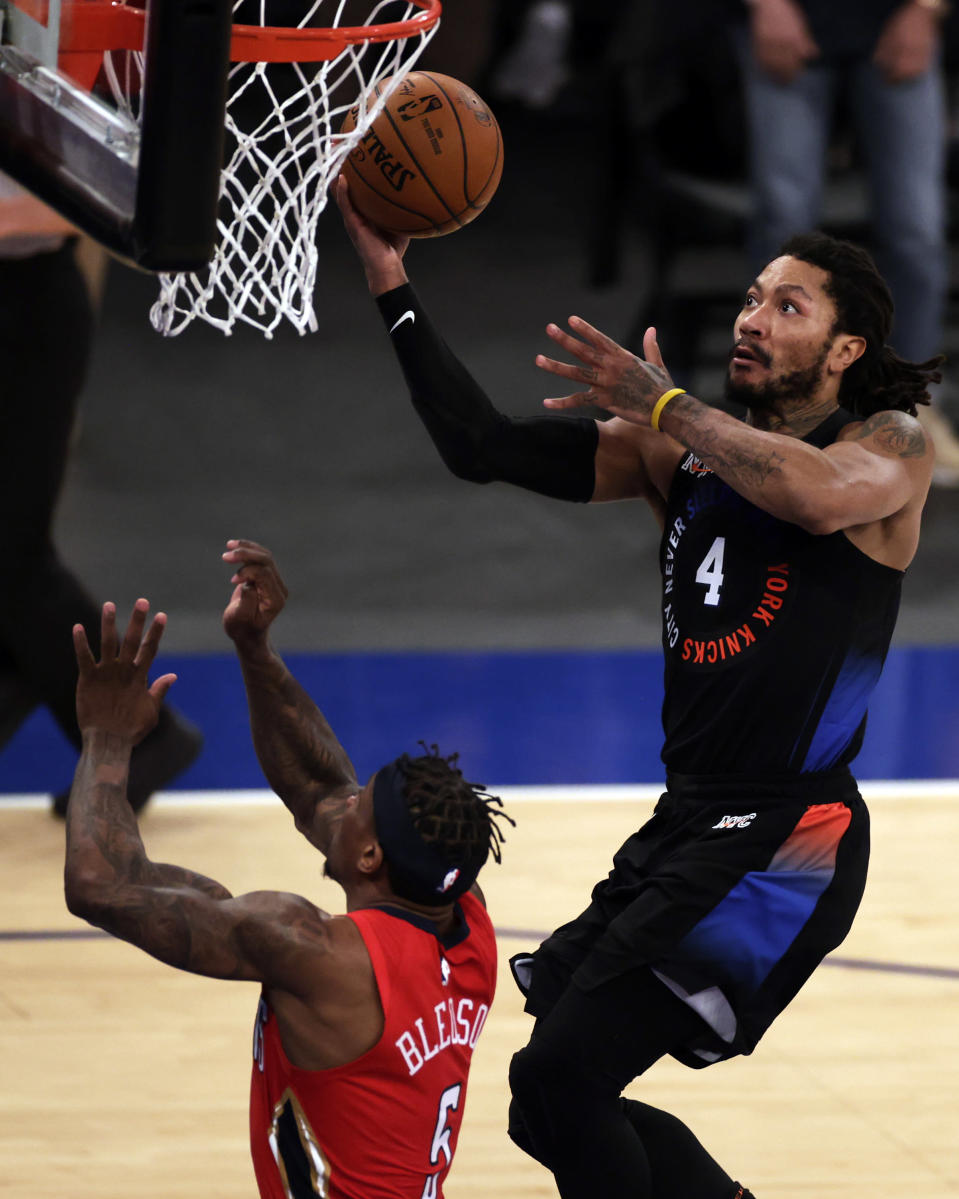New York Knicks guard Derrick Rose, right, drives to the basket past New Orleans Pelicans guard Eric Bledsoe, left, during overtime of an NBA basketball game Sunday, April 18, 2021, in New York. (AP Photo/Adam Hunger, Pool)