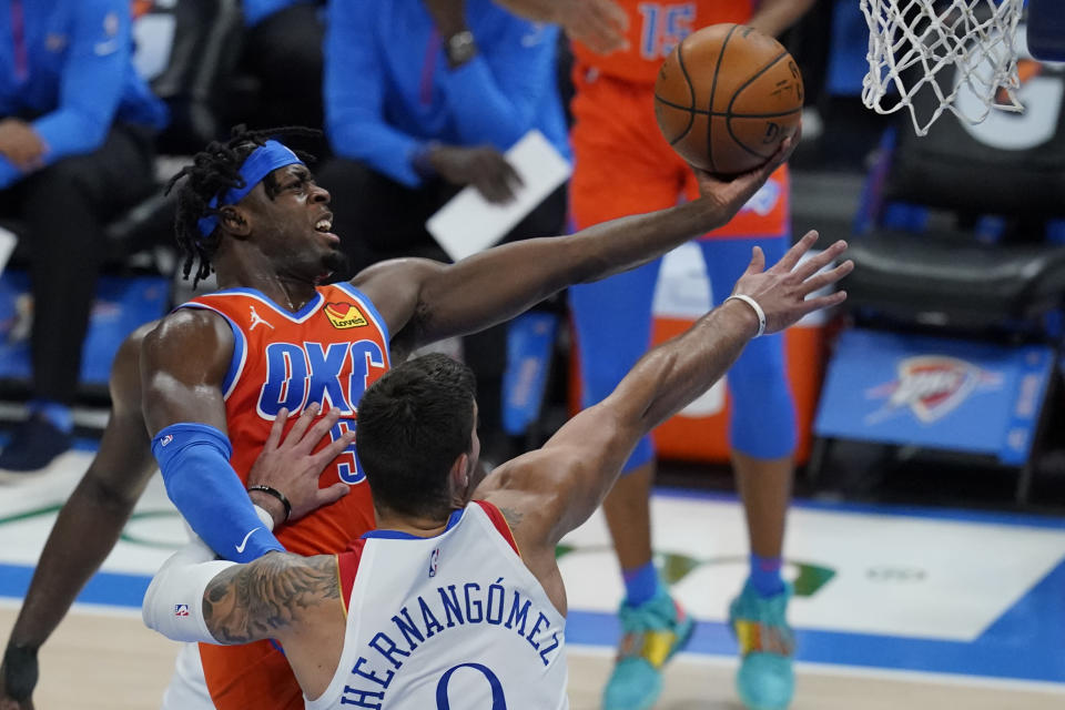 FILE - Oklahoma City Thunder forward Luguentz Dort, left, goes up for a shot in front of New Orleans Pelicans center Willy Hernangomez in Oklahoma City, in this April 29, 2021, file photo. Oklahoma City saw significant improvements from two of its young cornerstones in third-year guard Shai Gilgeous-Alexander and second-year guard Lu Dort.(AP Photo/Sue Ogrocki, File)