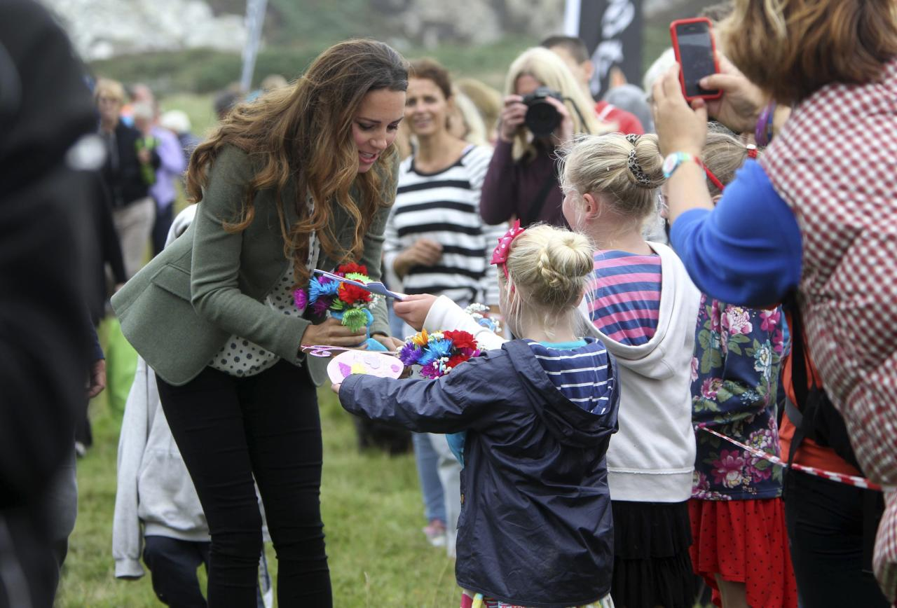 Britain's Catherine, Duchess of Cambridge receives cards from wellwishers during her visit to the Breakwater country park, to start the Ring O Fire ultra marathon, in Anglesey, north Wales August 30, 2013. REUTERS/Paul Lewis/pool (BRITAIN - Tags: ROYALS ENTERTAINMENT SPORT ATHLETICS)