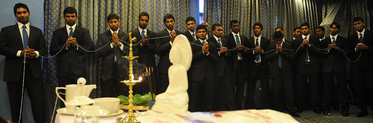 Sri Lankan cricketers watch as Buddhist monks chant prayers for their success during a ceremony in Colombo on October 14, 2011, prior to the team's departure for a cricket tour to the United Arab Emirates. (LAKRUWAN WANNIARACHCHI/AFP/Getty Images)