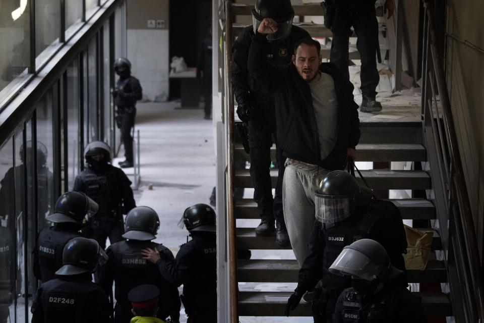 Rap singer Pablo Hasél is detained by police officers at the University of Lleida, Spain, Tuesday, Feb. 16, 2021. A 24-hour standoff between police and a rapper barricaded with dozens of his supporters in a university ended with the arrest of the artist, who has been sentenced to 9 months in prison for insulting the monarchy and praising terrorism. (AP Photo/Joan Mateu)