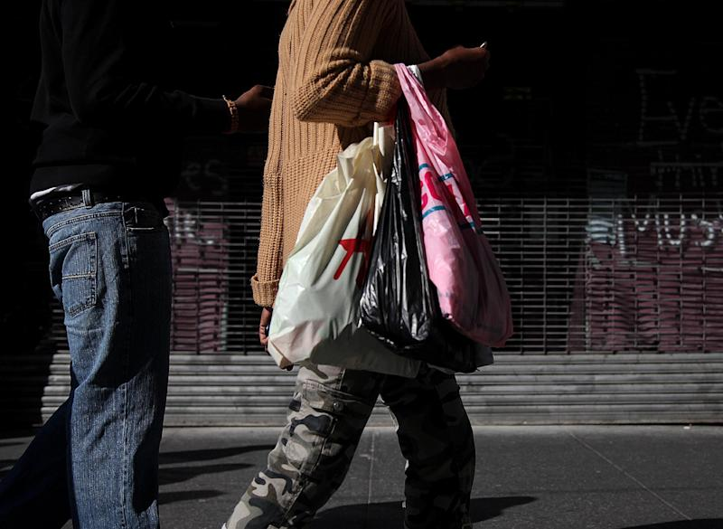 In this May 6, 2012, photo, shoppers carry their purchases along 33rd Street in New York. U.S. consumers barely increased their spending on retail goods in April. The weak gain was affected by cheaper gas prices and possibly a mild winter, which may have encouraged consumers to make purchases in the previous two months. The Commerce Department says retail sales rose 0.1 percent April. Retail spending had risen 0.7 percent in March and 1 percent in February. (AP Photo/CX Matiash)