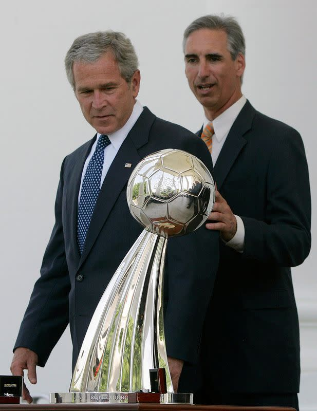 FILE PHOTO: U.S. President Bush and Houston Dynamo President and General Manager Luck look at the MLS championship trophy before posing for a picture with the team in Washington