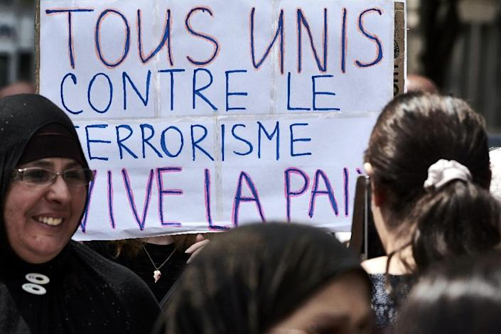 """Demonstrators hold a placard reading """"All united against terrorism, long live to peace"""" at a silent march in Lyon on July 30, 2016 (AFP Photo/Jean-Philippe Ksiazek )"""
