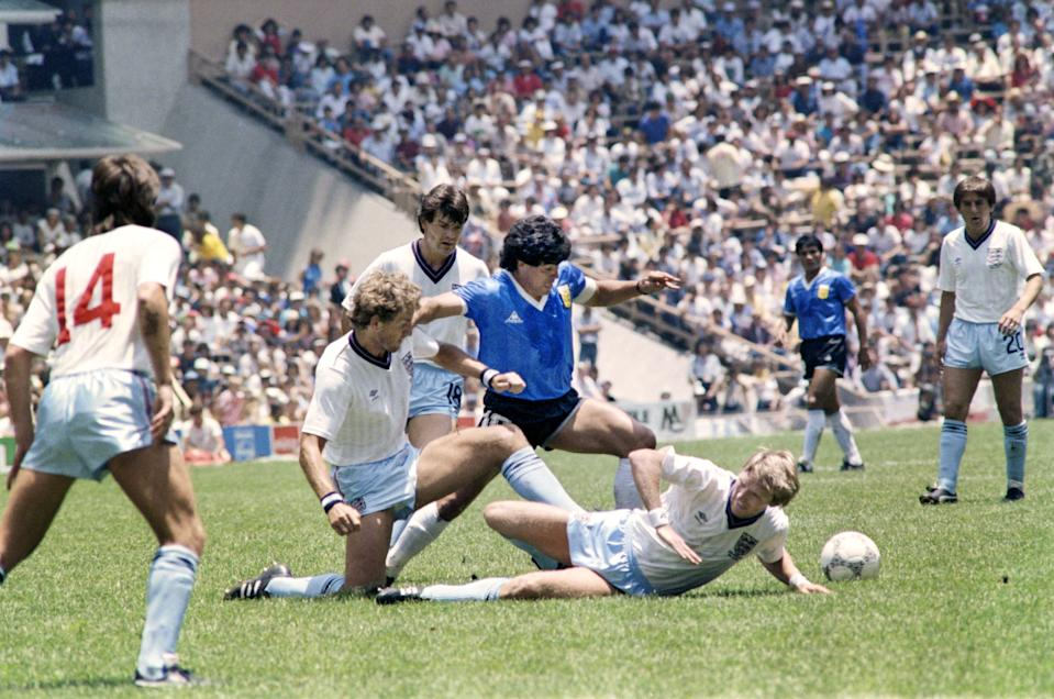 Argentinian midfielder Diego Maradona (C) dribbles past three English defenders on June 22, 1986 in Mexico City during the World Cup quarterfinal soccer match between Argentina and England. Maradona scored two goals, the first one with his left hand as he jumped for the ball in front of goalkeeper Peter Shilton, as Argentina beat England 2-1. (Photo by STAFF / AFP)        (Photo credit should read STAFF/AFP via Getty Images)