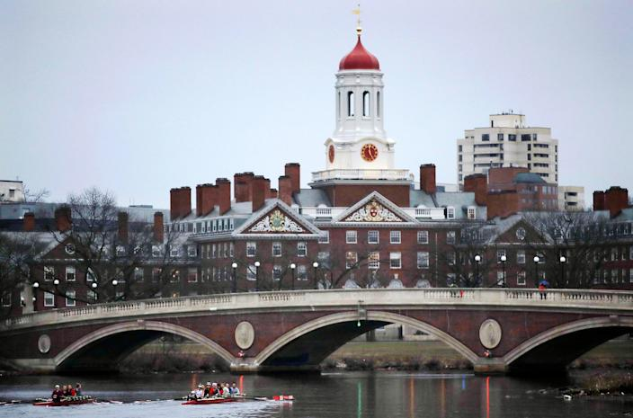 In this March 7, 2017, file photo, rowers paddle along the Charles River past the Harvard University campus in Cambridge, Mass.