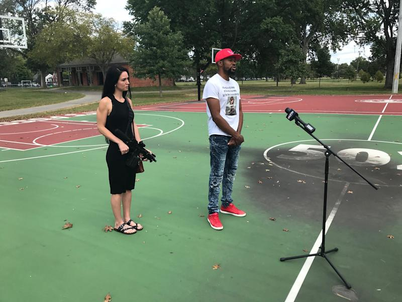 Kendrik Wilson, right, talks to media Sunday about his social media posts on the Breonna Taylor investigation while his friend Julia Robert holds a gun at Wyandotte Park south of Churchill Downs.