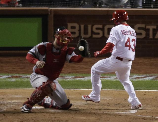 St. Louis Cardinals' Shane Robinson scores as Boston Red Sox catcher David Ross takes the throw during the seventh inning of Game 4 of baseball's World Series Sunday, Oct. 27, 2013, in St. Louis. Robinson scored on a hit by Matt Carpenter. (AP Photo/Charlie Riedel)