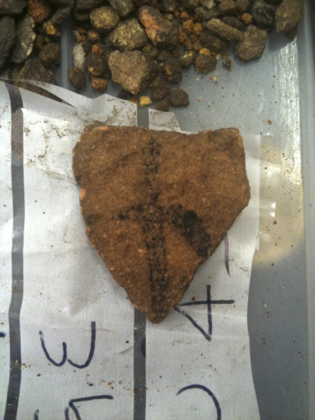 In this May 2012 photo provided by Bryce Barker, a fragment of Aboriginal rock art on granite found in Australian Outback is seen on a plastic bag. University of Southern Queensland archaeologist Bryce Barker said Monday, June 18, 2012 that tests show the Aboriginal rock art in the cave was made 28,000 years ago, making it the oldest in Australia and among the oldest in the world. The rock art was made with charcoal, so radiocarbon dating could be used to determine its age. (AP Photo/Bryce Barker) EDITORIAL USE ONLY