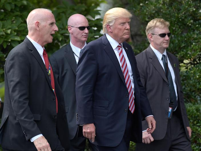 President Donald Trump, his longtime bodyguard Keith Schiller, left, and two Secret Service agents walk along the South Lawn of the White House: AP