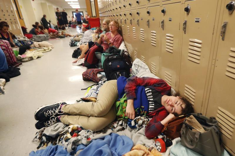 FILE - In this Oct. 10, 2018 file photo, Emily Hindle lies on the floor at an evacuation shelter set up at Rutherford High School, in advance of Hurricane Michael, in Panama City Beach, Fla. Local officials across the South are still scurrying to fix their hurricane evacuation and sheltering plans because of changes needed due to coronavirus and a cratering economy.  (AP Photo/Gerald Herbert, File)