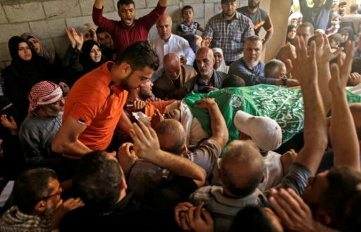 Palestinian mourners carry the body of 51-year-old Nasser Ghorab at his funeral in a refugee camp in the central Gaza Strip on May 16, 2018, a day after he was killed along during protests the border with Israel