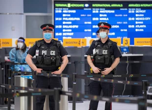 Police and workers wait for arrivals at the COVID-19 testing centre at Pearson airport in Toronto on Feb. 3. The Public Health Agency of Canada says it's 'aware' of 513 tickets being issued to air passengers between Feb. 22 and April 25 who landed in Toronto or Vancouver and refused quarantine in a hotel.  (Frank Gunn/The Canadian Press - image credit)