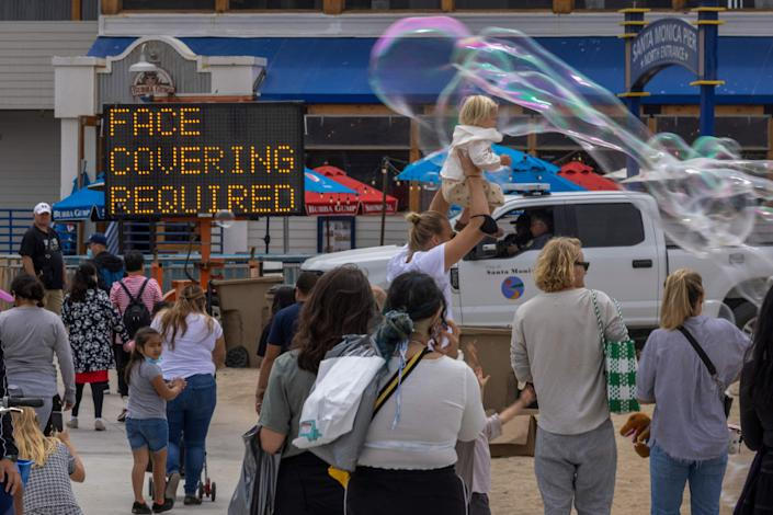 People walk past bubbles near the Santa Monica Pier as crowds gather on Memorial Day as shutdowns are relaxed more than a year after Covid-19 pandemic shutdowns began, in Santa Monica, California on May 31, 2021. (Photo by DAVID MCNEW / AFP) (Photo by DAVID MCNEW/AFP via Getty Images)