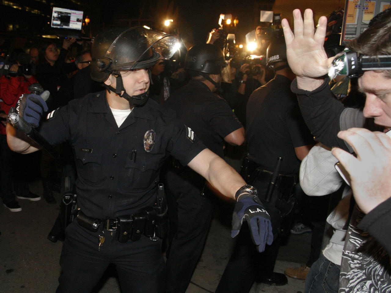 A Los Angeles Police officer orders an anti-Wall Street protester off the street at the Occupy LA camp in Los Angeles on Monday, Nov. 28, 2011. Los Angeles Mayor Antonio Villaraigosa stated Friday that the protestors's campsite will be dismantled, beginning at 12:01 a.m., Monday, but police did not enforce the deadline. (AP Photo/Jason Redmond)