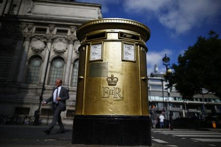 A man walks past a golden Royal Mail post box in Westminster, central London, October 8, 2013. REUTERS/Andrew Winning