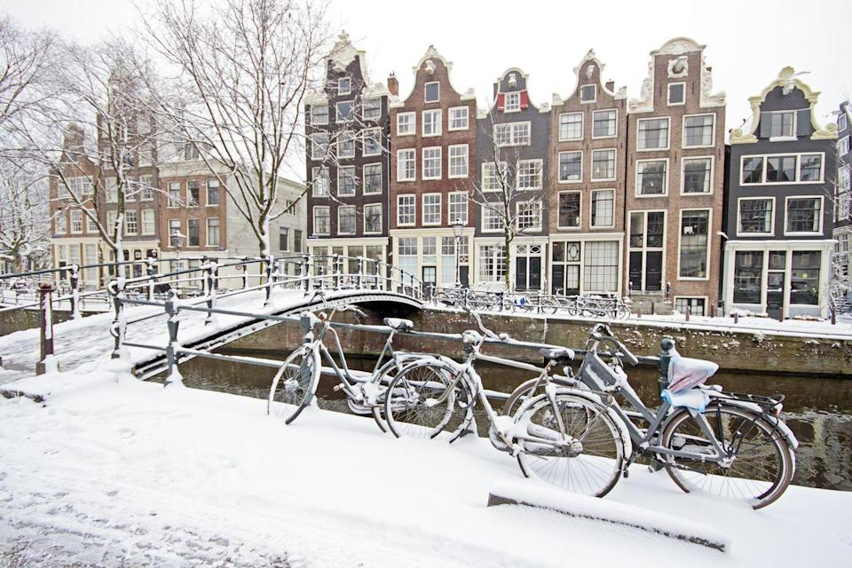 <p>Snow-covered bikes line the canal in Amsterdam.</p>