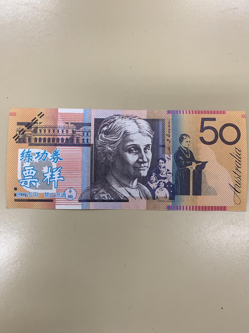 Pictured is a counterfeit $50 note with blue foreign writing in the bottom left corner. Source: Queensland Police