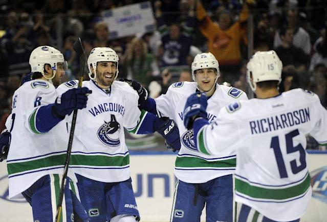 Vancouver Canucks right winger Brad Richardson (15) celebrates his goal with defenseman Christopher Tanev (8), Jason Garrison (5) and center Mike Santorelli (25) during the second period of an NHL hockey game in Buffalo, N.Y., Thursday, Oct. 17, 2013. (AP Photo/Gary Wiepert)
