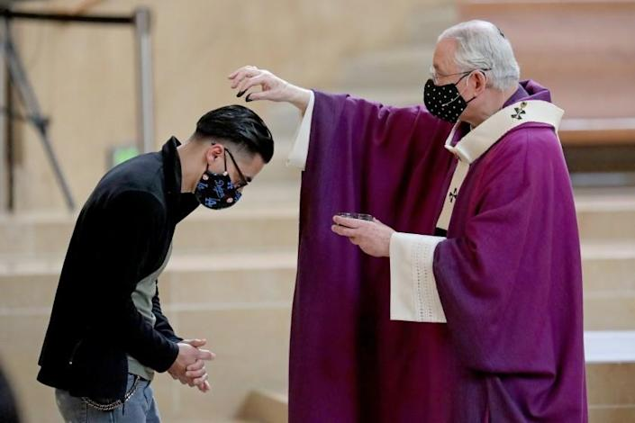 LOS ANGELES, CA - FEBRUARY 17: A parishioner receives ashes sprinkled on her head from Archbishop of Los Angeles Jose Gomez on Ash Wednesday at the Cathedral of Our Lady of the Angels on Wednesday, Feb. 17, 2021 in Los Angeles, CA. Archbishop of Los Angeles Jose Gomez presided over the service. The coronavirus pandemic will force a change in the distribution of ashes for Ash Wednesday at Roman Catholic churches. Ashes will be sprinkled on the heads of parishioners. (Gary Coronado / Los Angeles Times)