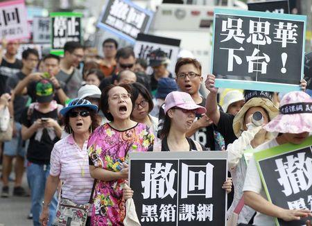 Activists march on the street during a protest in front of the Ministry of Education in Taipei, Taiwan, August 2, 2015. REUTERS/Pichi Chuang