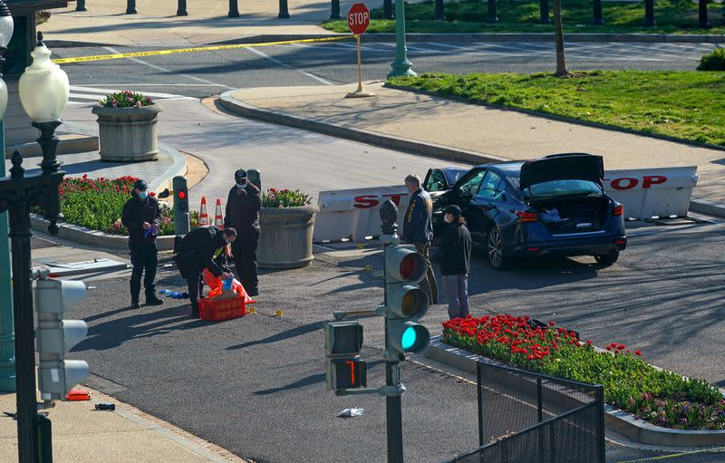 Law enforcement officers collect evidence at the site after a car rammed a police barricade outside the U.S. Capitol building on Capitol Hill in Washington
