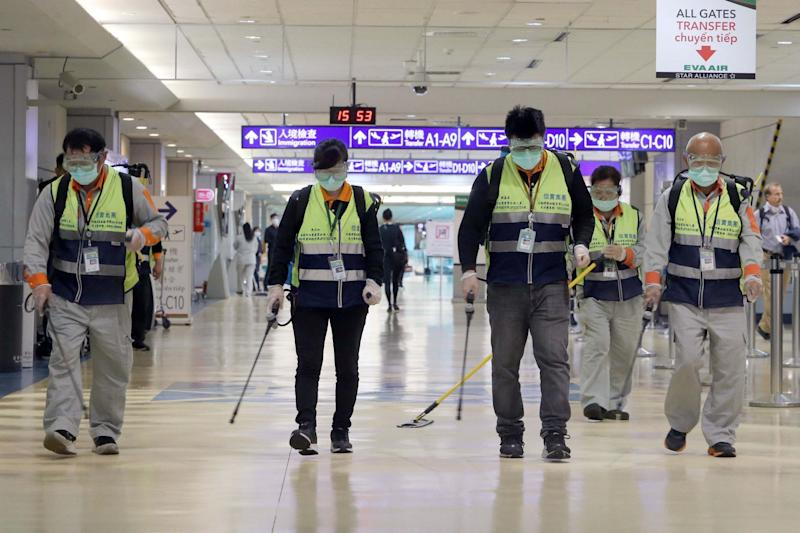 Masked workers disinfect a passenger thoroughfare at the Taoyuan International Airport (AFP via Getty Images)