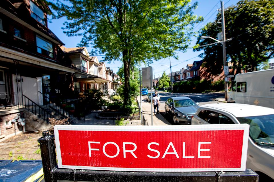 For sale sign is displayed outside a home in Toronto, Ontario, Canada June 15, 2021. REUTERS/Carlos Osorio