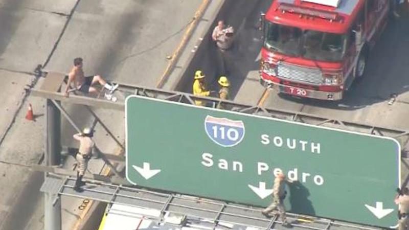 Nearly Naked Man Climbs L A  Freeway Sign, Stops Rush Hour