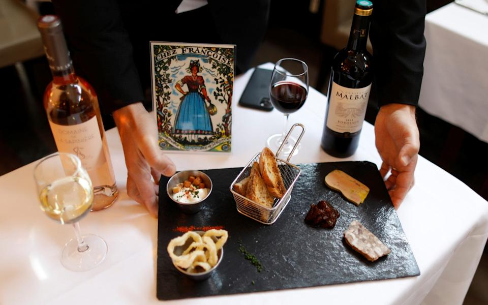 """Pascal Mousset, owner of """"Chez Francoise"""" restaurant, displays an """"after-work menu"""" created to be served before the evening curfew, - Charles Platiau/Reuters"""
