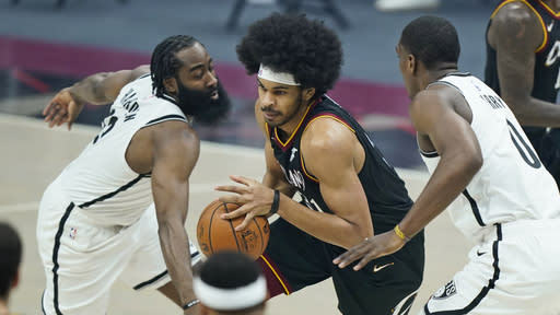Cleveland Cavaliers' Jarrett Allen, center, drives between Brooklyn Nets' James Harden, left, and Reggie Perry, right, during the first half of an NBA basketball game, Wednesday, Jan. 20, 2021, in Cleveland. (AP Photo/Tony Dejak)