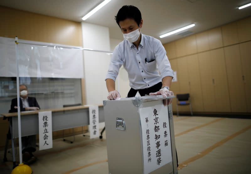 A member of Election Management Committee wearing a protective face mask and vinyl gloves disinfect a ballot box amid the coronavirus disease (COVID-19) outbreak, at a voting station for the Tokyo Governor election in Tokyo